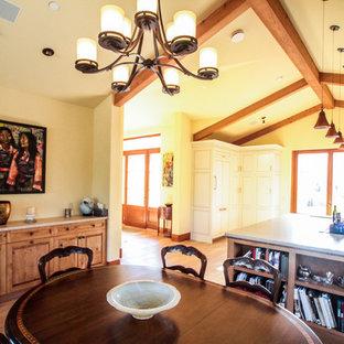 Foto di una sala da pranzo aperta verso la cucina mediterranea di medie dimensioni con pareti gialle, pavimento in legno massello medio, camino classico, cornice del camino in intonaco e pavimento marrone