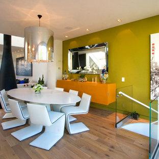 Modelo de comedor contemporáneo, de tamaño medio, abierto, con paredes verdes, suelo de madera en tonos medios, marco de chimenea de metal y chimeneas suspendidas