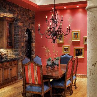Diseño de comedor mediterráneo con paredes rojas y suelo de madera en tonos medios