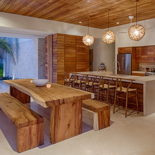 Cette photo montre une grand salle à manger ouverte sur la cuisine exotique avec un mur gris.