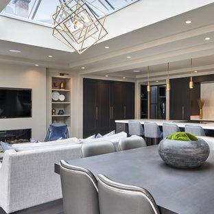 Immagine di una grande sala da pranzo aperta verso il soggiorno contemporanea con parquet scuro, camino sospeso, cornice del camino in intonaco e pavimento grigio