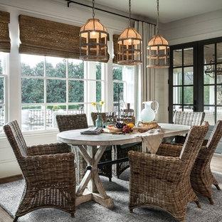 Modelo de comedor de estilo de casa de campo, grande, sin chimenea, con suelo de madera clara y paredes blancas