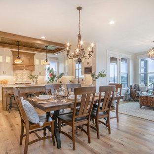 Esempio di una sala da pranzo aperta verso il soggiorno chic con pareti bianche, pavimento in vinile e pavimento marrone