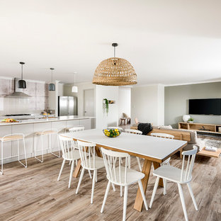 This is an example of a mid-sized contemporary open plan dining in Perth with grey walls, laminate floors and brown floor.