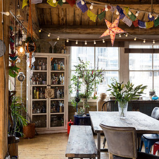 Bohemian open plan dining room in London with brown walls, light hardwood flooring and beige floors.