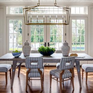 Enclosed dining room - beach style medium tone wood floor enclosed dining room idea in Boston with white walls
