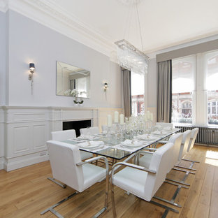 Design ideas for a medium sized traditional enclosed dining room in London with light hardwood flooring, a standard fireplace, beige floors and grey walls.