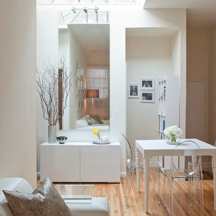 Example of a minimalist medium tone wood floor dining room design in New York with white walls