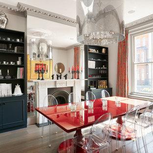 Idée de décoration pour une salle à manger bohème fermée et de taille moyenne avec un mur blanc, un sol en bois brun, une cheminée standard et un manteau de cheminée en pierre.