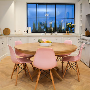 Photo of a medium sized scandi kitchen/dining room in London with light hardwood flooring, white walls and beige floors.