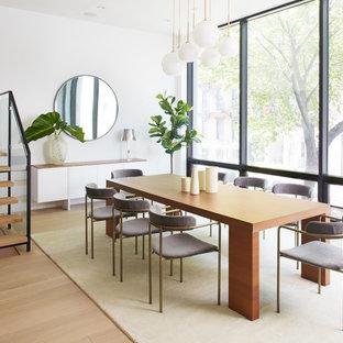 Cette image montre une très grande salle à manger design avec un mur blanc et un sol en bois clair.