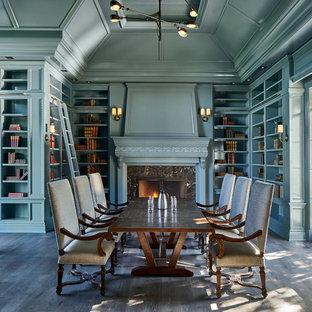 Inspiration pour une grande salle à manger traditionnelle avec un mur bleu, une cheminée standard, un sol marron, un sol en bois foncé et un manteau de cheminée en pierre.
