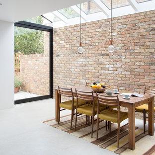 Immagine di una sala da pranzo aperta verso la cucina scandinava di medie dimensioni con pareti marroni e pavimento in cemento