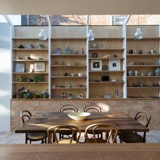 Cette image montre une salle à manger nordique de taille moyenne avec un mur marron, un sol en brique et un sol orange.