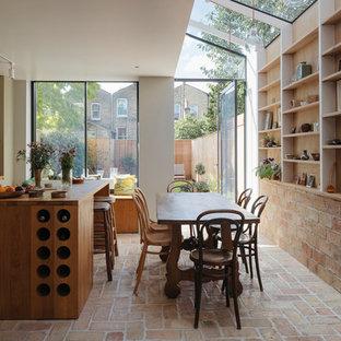 Inspiration pour une salle à manger ouverte sur la cuisine minimaliste de taille moyenne avec un mur beige, un sol en brique et un sol orange.