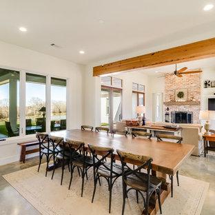 Idee per una grande sala da pranzo aperta verso il soggiorno country con pareti bianche, pavimento in cemento, camino classico, cornice del camino in mattoni e pavimento grigio