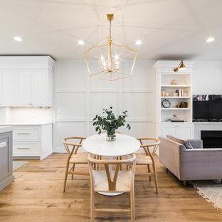 Foto di una sala da pranzo aperta verso il soggiorno classica di medie dimensioni con pareti bianche, parquet chiaro, camino classico, cornice del camino in cemento e pavimento marrone