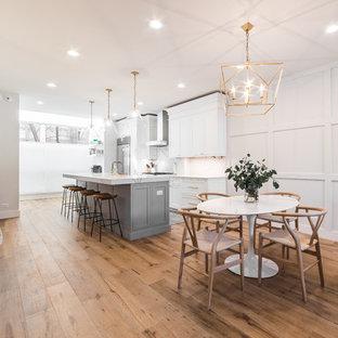 Immagine di una grande sala da pranzo aperta verso il soggiorno chic con pareti bianche, pavimento in legno massello medio, camino classico, cornice del camino in cemento e pavimento marrone