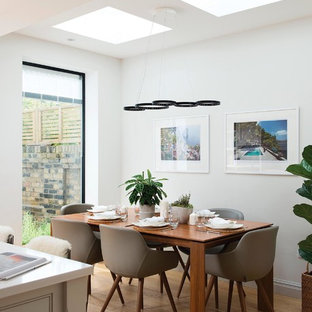 This is an example of a medium sized contemporary kitchen/dining room in London with white walls, light hardwood flooring, beige floors and no fireplace.