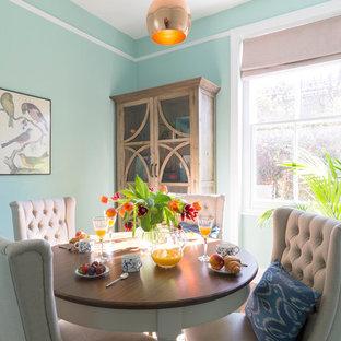 Modern inredning av en mellanstor separat matplats, med blå väggar och mellanmörkt trägolv