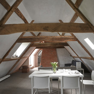 This is an example of a farmhouse open plan dining room in London with white walls, carpet and grey floors.