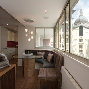 Photo of a medium sized contemporary dining room in London with white walls, medium hardwood flooring and brown floors.