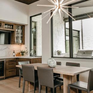 Immagine di una grande sala da pranzo aperta verso la cucina contemporanea con pareti bianche, pavimento beige e pareti in legno