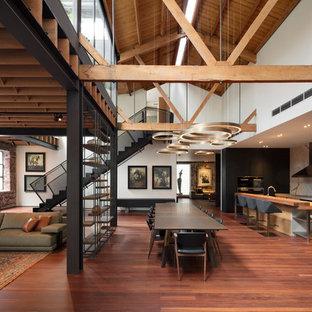 Diseño de comedor industrial, grande, abierto, con paredes blancas, suelo de madera en tonos medios y suelo marrón