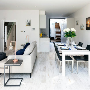 Photo of a medium sized contemporary open plan dining room in London with white walls, white floors and painted wood flooring.