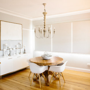 This is an example of a transitional dining room in Sydney with medium hardwood floors.