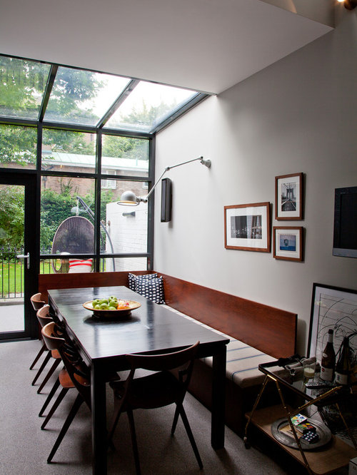 Example Of A Trendy Dining Room Design In London With White Walls