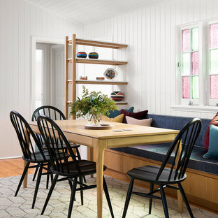 This is an example of a transitional dining room in Brisbane with white walls, medium hardwood floors and brown floor.