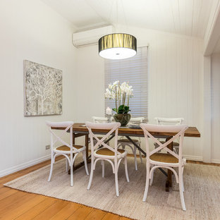 Inspiration for a beach style separate dining room in Brisbane with white walls, medium hardwood floors and beige floor.