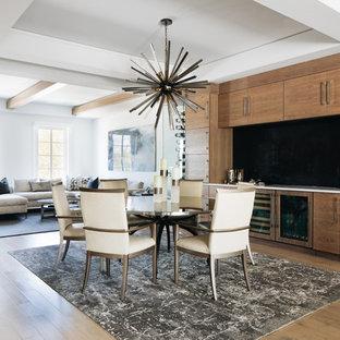 Imagen de comedor actual, de tamaño medio, abierto, con paredes grises, suelo de madera clara, chimenea tradicional y marco de chimenea de metal