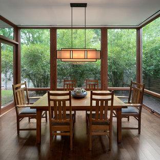 Aménagement d'une salle à manger craftsman fermée avec un sol en bois foncé.