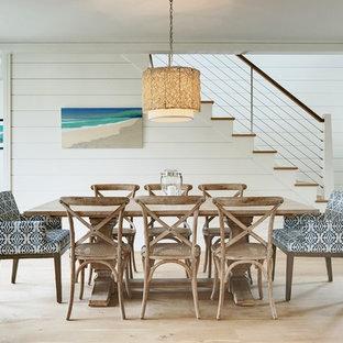 Imagen de comedor costero con paredes blancas, suelo de madera clara y suelo beige