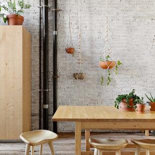Esempio di una grande sala da pranzo aperta verso la cucina industriale con pareti bianche, pavimento in legno massello medio, camino classico, cornice del camino in legno e pavimento marrone