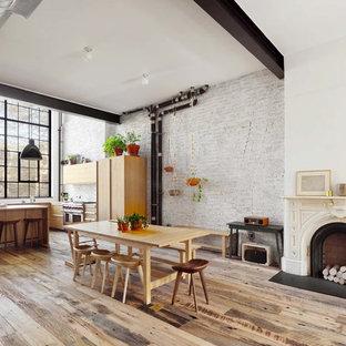 Ejemplo de comedor de cocina urbano, grande, con paredes blancas, suelo de madera en tonos medios, chimenea tradicional, marco de chimenea de madera y suelo marrón