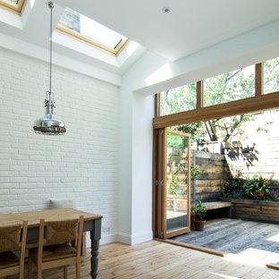 Immagine di una sala da pranzo aperta verso la cucina design di medie dimensioni con pareti bianche e pavimento in legno massello medio