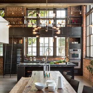 Esempio di una sala da pranzo aperta verso la cucina industriale di medie dimensioni con pareti multicolore, pavimento in cemento e nessun camino