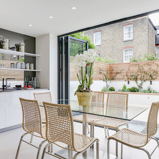 This is an example of a contemporary kitchen/dining room in London with white walls, no fireplace and white floors.