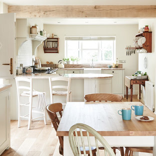 Design ideas for a rural kitchen/dining room in Wiltshire with white walls, light hardwood flooring, no fireplace and beige floors.