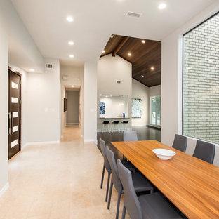 ダラスの広いモダンスタイルのおしゃれなダイニングキッチン (ベージュの壁、標準型暖炉、ベージュの床、コンクリートの暖炉まわり、磁器タイルの床) の写真
