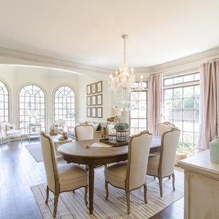 Foto di una sala da pranzo aperta verso il soggiorno tradizionale con pareti beige, parquet scuro e nessun camino