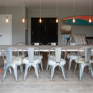 Design ideas for a large beach style enclosed dining room in Sussex with grey walls and light hardwood flooring.