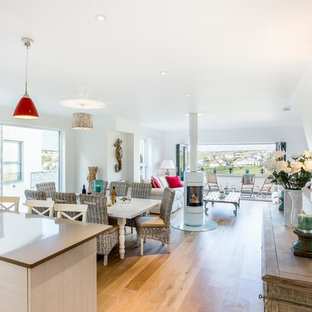 Photo of a beach style open plan dining room in Cornwall with white walls, medium hardwood flooring and a wood burning stove.