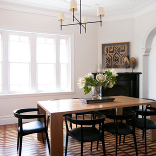 Foto di una sala da pranzo design chiusa con pareti bianche e camino ad angolo