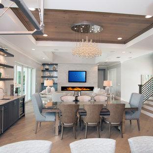 Cette image montre une grand salle à manger ouverte sur la cuisine design avec un mur gris, un sol en bois clair, une cheminée ribbon, un manteau de cheminée en pierre de parement, un sol marron et un plafond en bois.