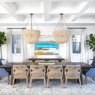 Immagine di una sala da pranzo aperta verso il soggiorno stile marinaro di medie dimensioni con pareti bianche, pavimento in legno massello medio, nessun camino e pavimento grigio