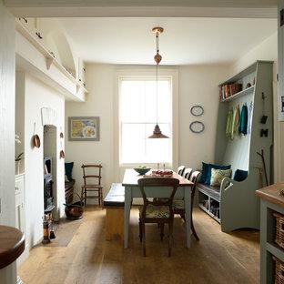 Идея дизайна: кухня-столовая в морском стиле с паркетным полом среднего тона, белыми стенами и печью-буржуйкой